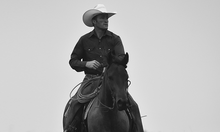 Byron Hogan: Wise Cowboy & Mustang Expert - For Byron Hogan, the strong wills of a wild horse and a wild boy are mirror images reflecting back a desire to be seen, respected and trusted.As the product of a broken home, Byron Hogan grew up somewhat detached and isolated. As a strong boy with a tender heart, it wasn't always easy for Byron to find an authentic connection with other people; but, he could always find unconditional understanding when he was around Mustangs. The process of taming a horse that has its guard up all the time takes a willingness to keep trying — even when the horse seems determined to break you. But when you share the same dogged will as the horse you are taming, a breakthrough is inevitable. As a result of his tenaciousness, Byron has become a renowned Mustang tamer, and a multi-time finalist in the Extreme Mustang Makeover Challenge, as well as the Reserve Champion of the premier event known as the Supreme Extreme Mustang Makeover. For five years, Byron has worked for the Mustang Heritage Foundation — a non-profit organization created to promote and protect the American wild Mustang from abuse and neglect.