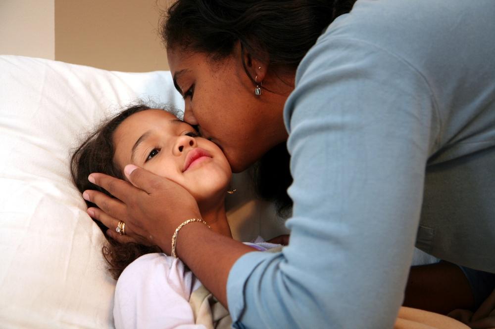 Mother tucking in daughter._6329344_M.jpg