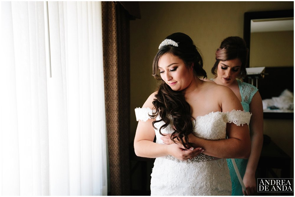 Bride getting ready by the window light, bridesmaid helping her get into the dress