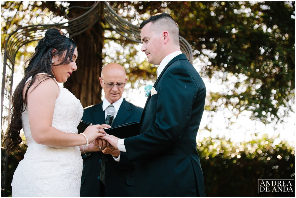 Bride putting on the ring to groom during ceremony