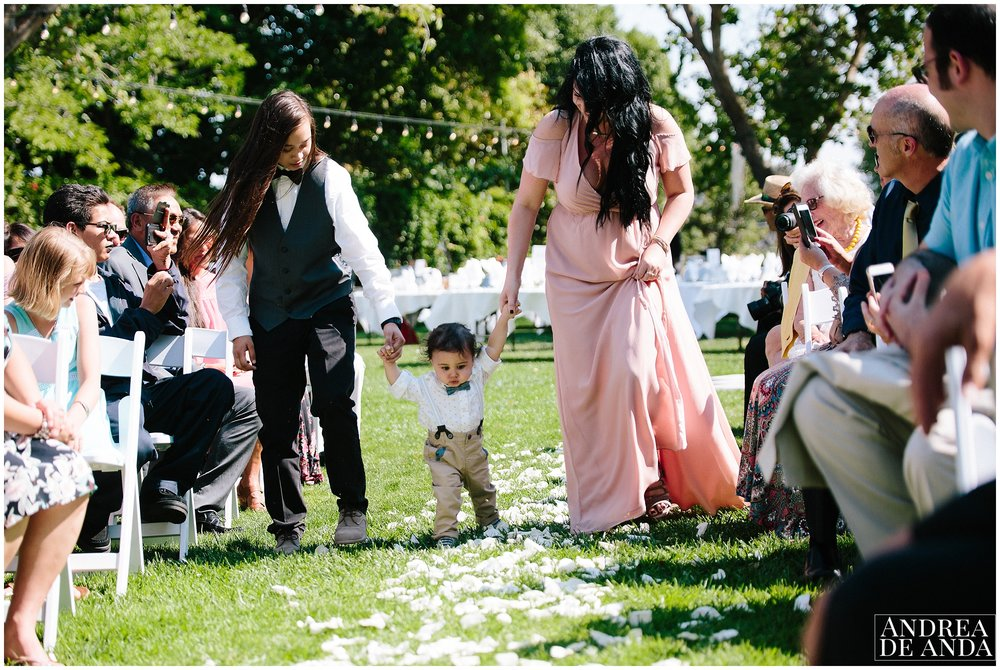baby boy walking down the aisle, Secret Garden wedding ceremony Madonna Inn wedding. San Luis Obispo Wedding Photographer