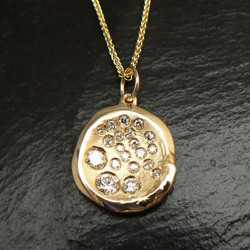 The family rings made into a custom pendant reusing the gold and diamonds.
