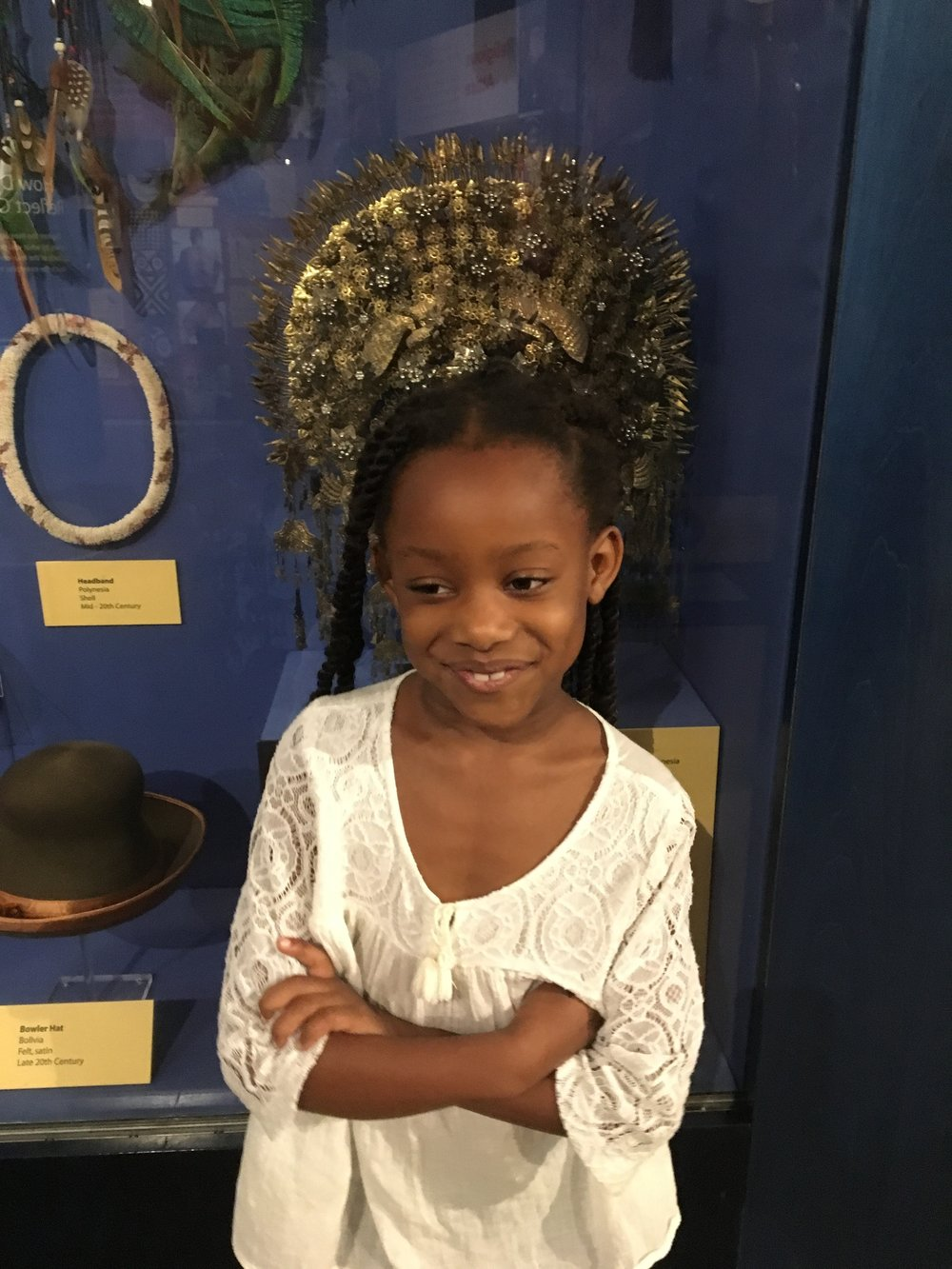Azariah in front of one of the many opulent headpieces on display in the Reflections of Culture exhibit.
