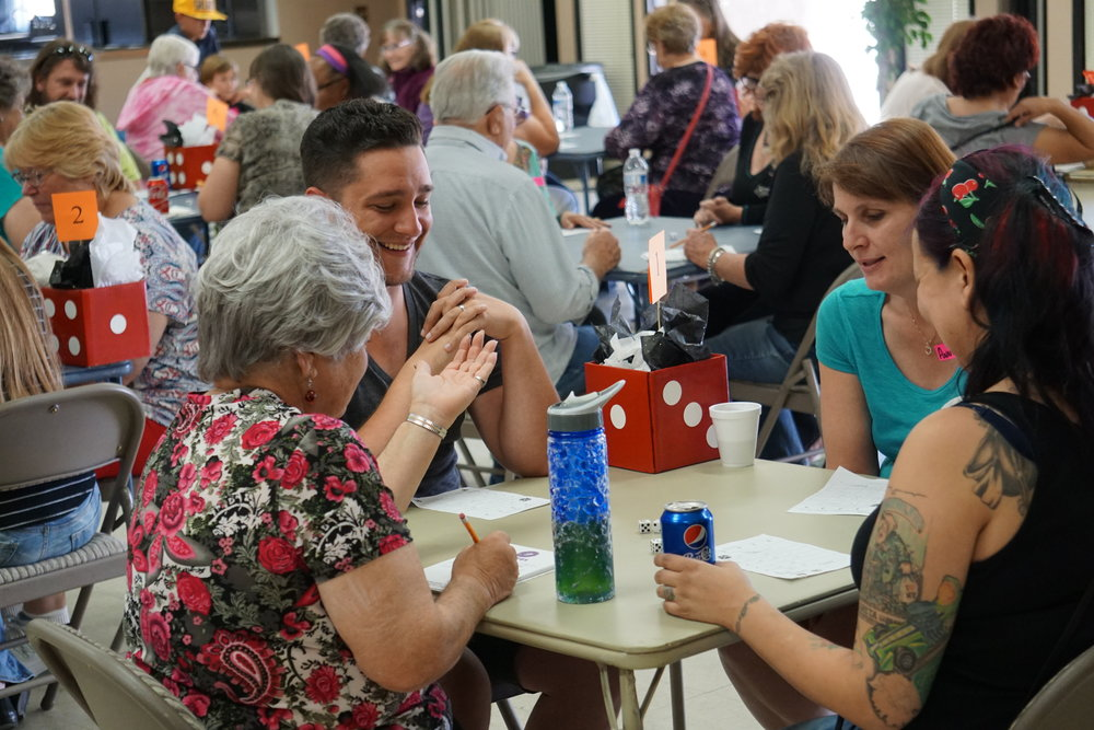 Dice rolling, people laughing, and then an excited yell, Bunco!  On Saturday, May 13, 2017, High Desert Homeless Services (HDHS), the local Homeless Shelter had a Bunco Tournament. With the gracious support of sponsors, including Trinity Lutheran Church, who generously offered their facility for our use, the fundraising event went amazingly. The event included a Oggi's pizza meal, with delicious pastries, and drinks for all. All was included in the small $20 donation. Those who wanted additional chances to win great prizes purchased raffle tickets for their chance to win camping gear, household items, donated prizes, gift baskets, and even a pair of Disneyland tickets. The room was filled with happy faces, excitedly rolling the dice to see if they might be a winner. Prizes were provided by MMEC, HDHS Board Secretary Karen Maxwell, Oggi's Pizza, Nanas Pearls, A Touch for Your Health Massage, Home Depot, Walmart, and Disneyland. Volunteers included the Serrano High School Socially Aware Club, who did an amazing job helping to set up, directing attendees to parking, and serving food and drinks to those playing. The winner of the most Buncos went home with $200 in cash and even the person with the most losses got a prize. If you missed this Bunco event, there are more coming soon. Upcoming events are on June 10th and July 8th. Anyone who would like to reserve their seat or if you have any other questions you can call (760)245-5991. High Desert Homeless Services still needs business cash and prize sponsors for the future events. If you would be willing to make a difference by becoming a sponsor, please call or email (760)245-5991 or highdeserthomeless@yahoo.com.