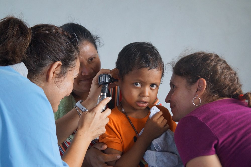 Parishioner Dr Romero peers into a child's ear who probably hasn't seen a doctor her whole life as a villager in the mountains of Honduras.