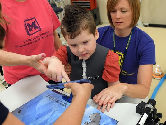 A 7-year-old patient uses SpellBound with his Occupational and Physical therapists. Photo: Lon Horwedel / Special to The Detroit News