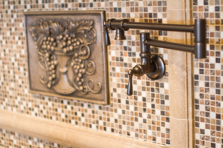 Mosaic Tiles With Warm Browns And Golds Help To Accent This Bronze Metal Backsplash Medallion