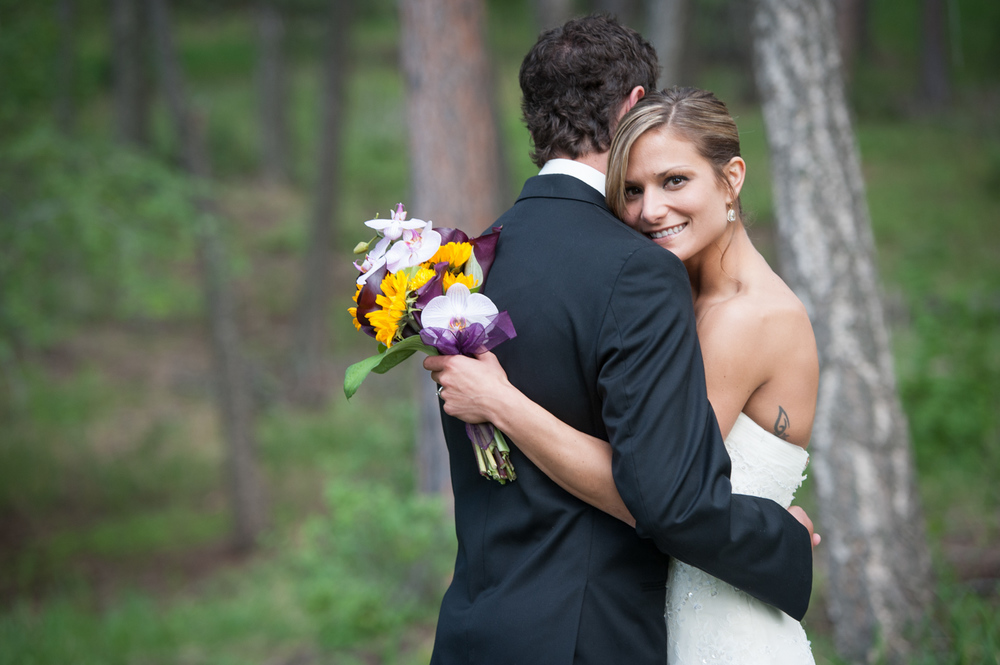 Bride smiles among Pine Trees during Colorado Mountain Wedding