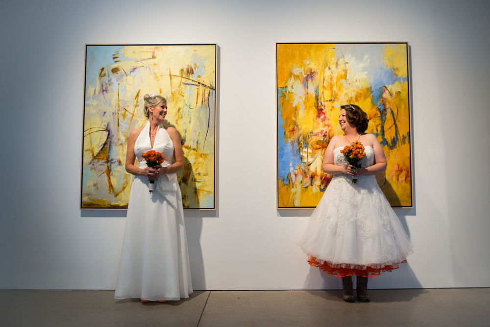 Brides stand in front of Art Wall at Denver Space Gallery LGBT Wedding