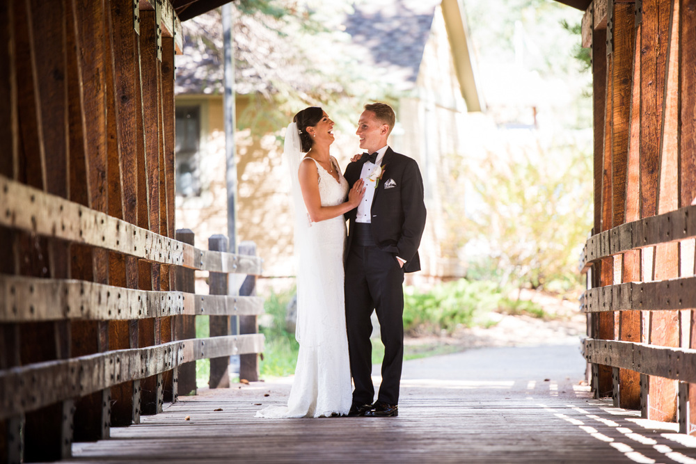 Bride and Groom laugh on sunny Vail bridge
