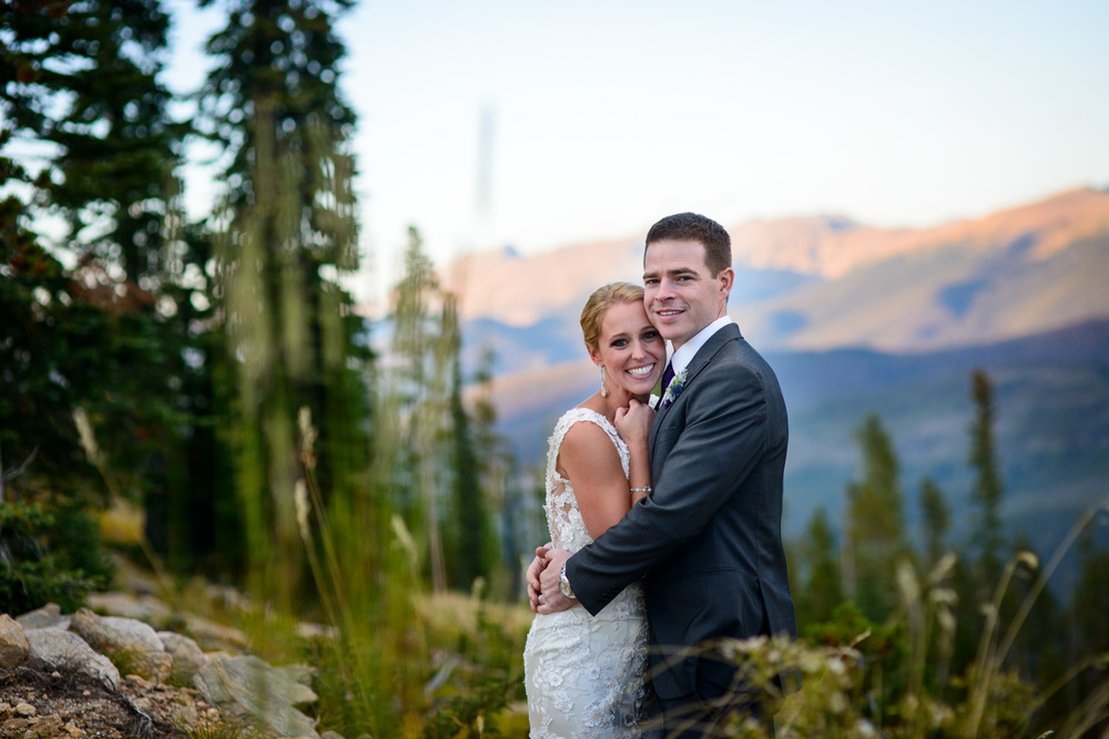 Bride and Groom pose in front of mountain sunset in Winter Park