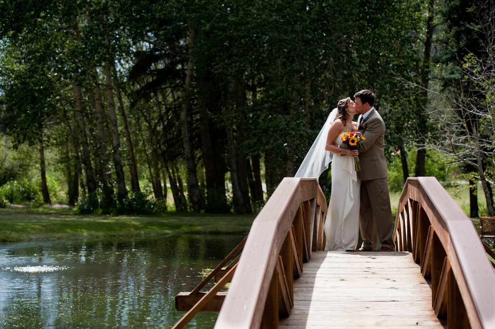 Bride and Groom kiss on Bridge in Estes Park, CO