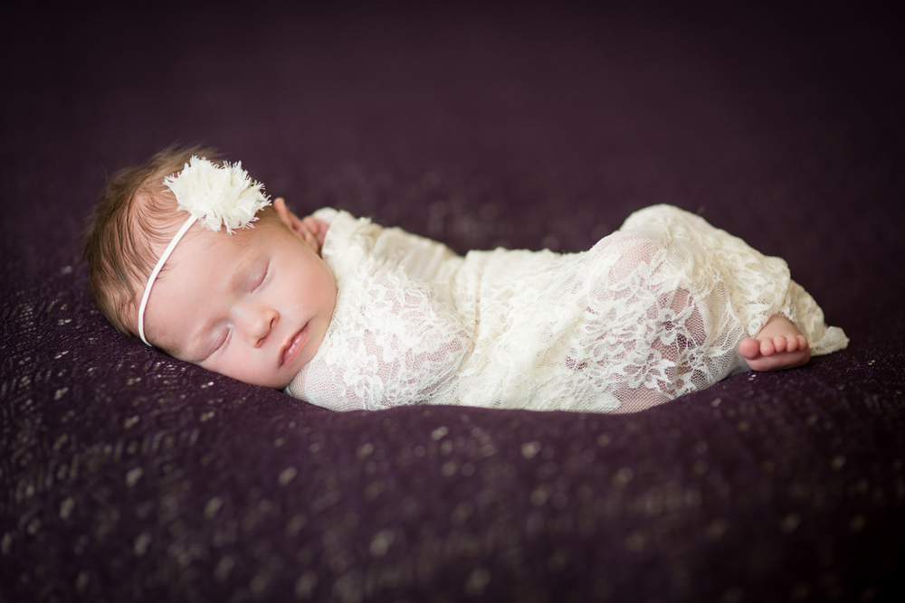 newborn baby girl poses on purple blanket with lace in Denver