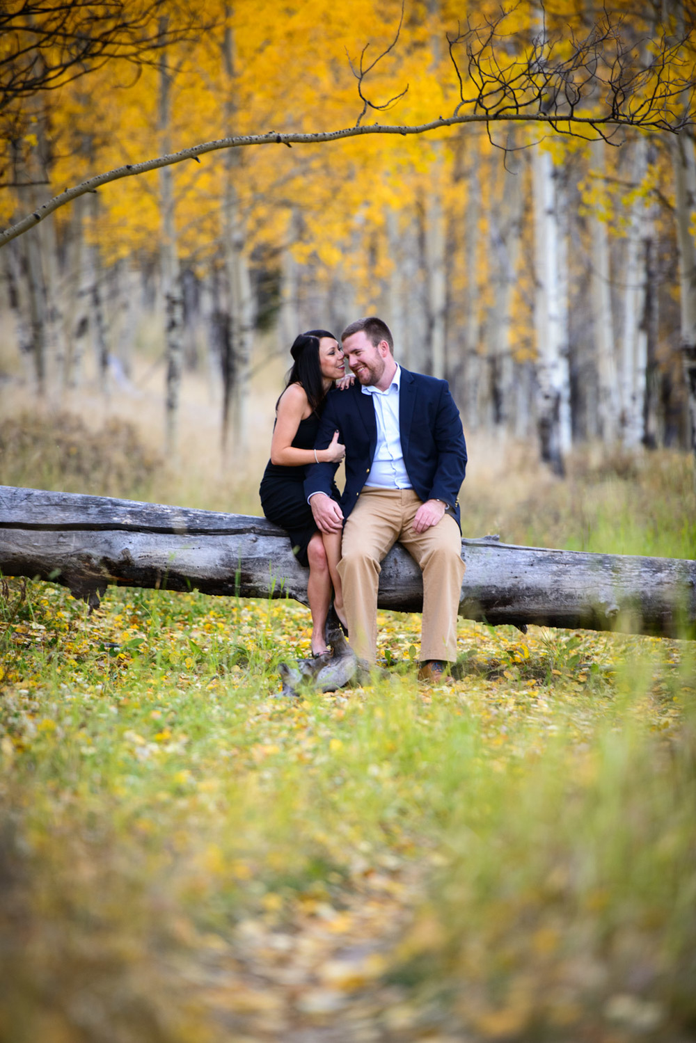 couple sits on tree branch in Fall at Kenosha Pass