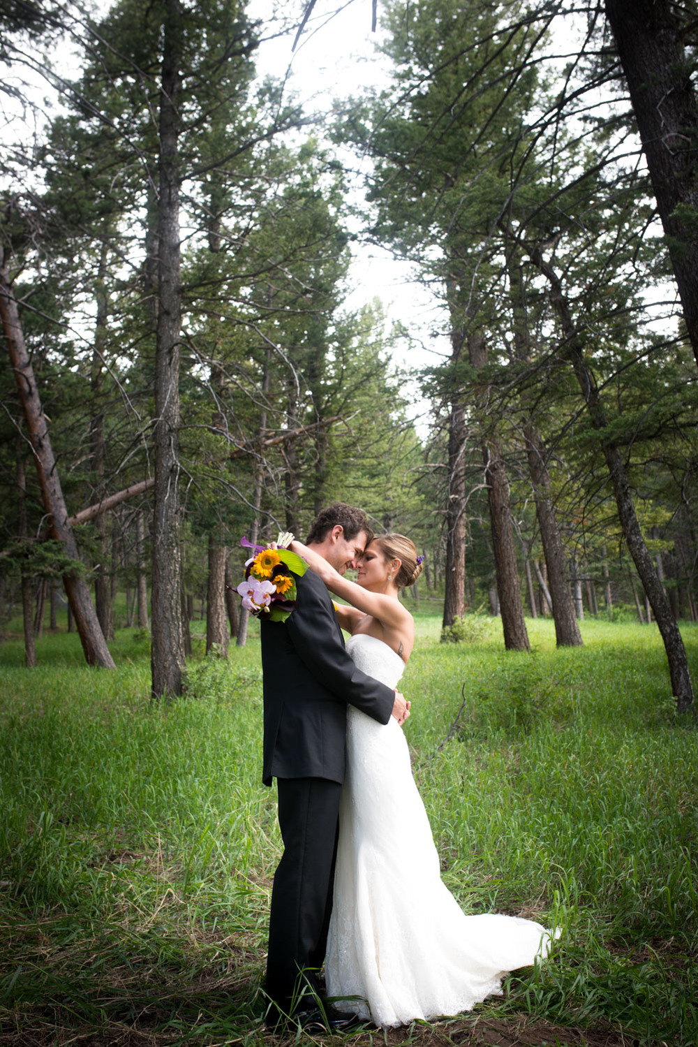 bride and groom embrace in colorado forest near Genesee Pines