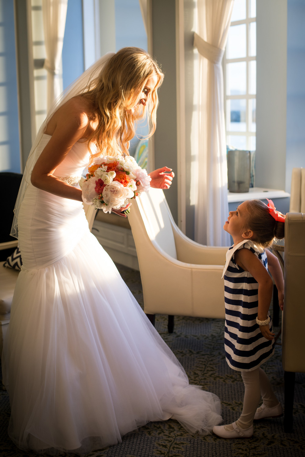 Bride talks with Flower girl in lobby pretty light