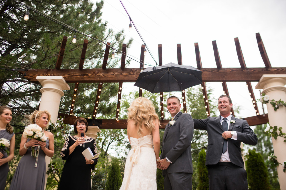 Groomsmen holds umbrella over Groom in rainy ceremony