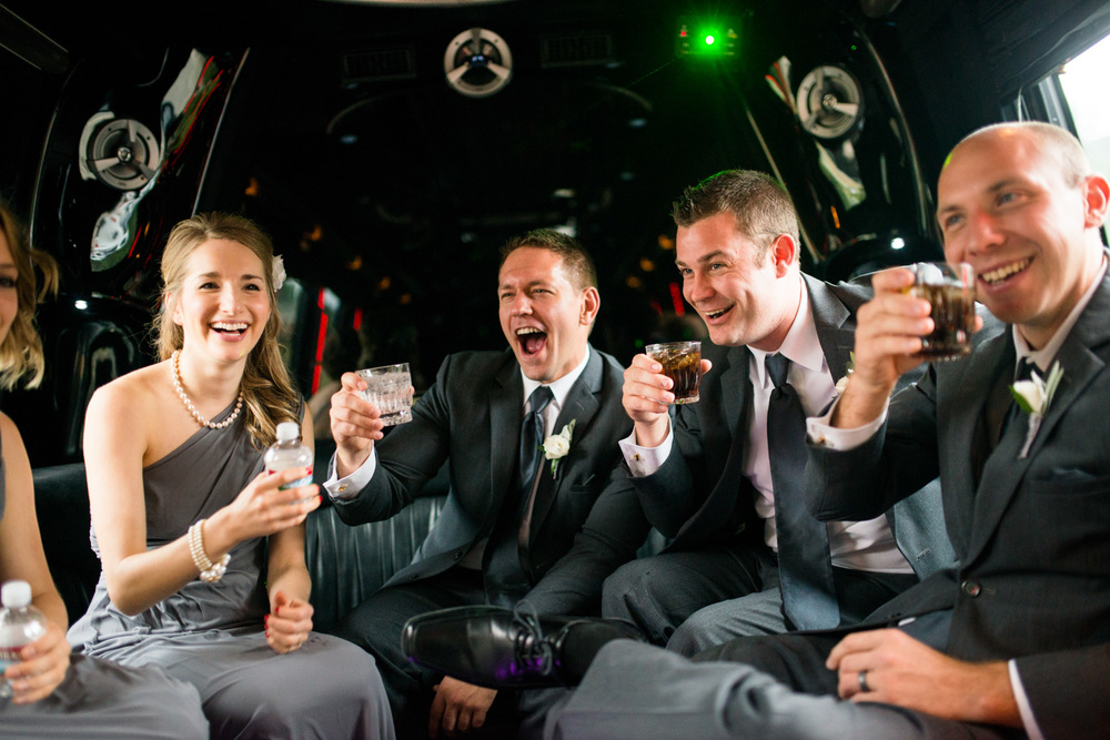 Colorado Wedding bridal party toast and laugh in limo