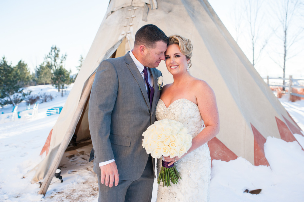 Bride and groom in front of Teepee in Winter wedding