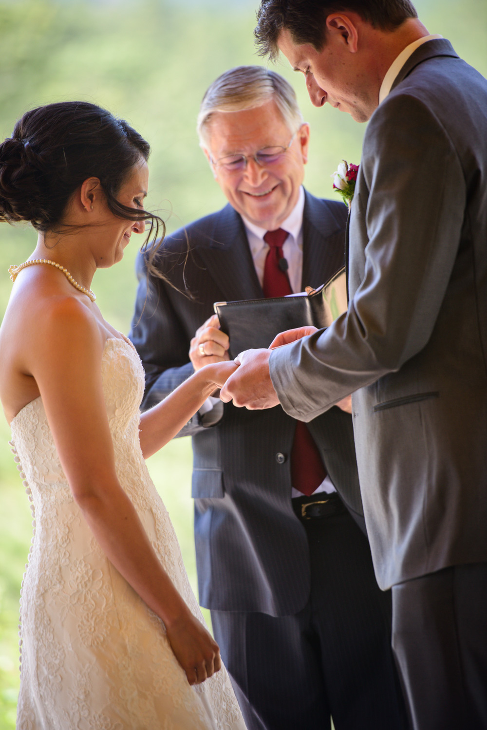 Groom puts ring on Bride