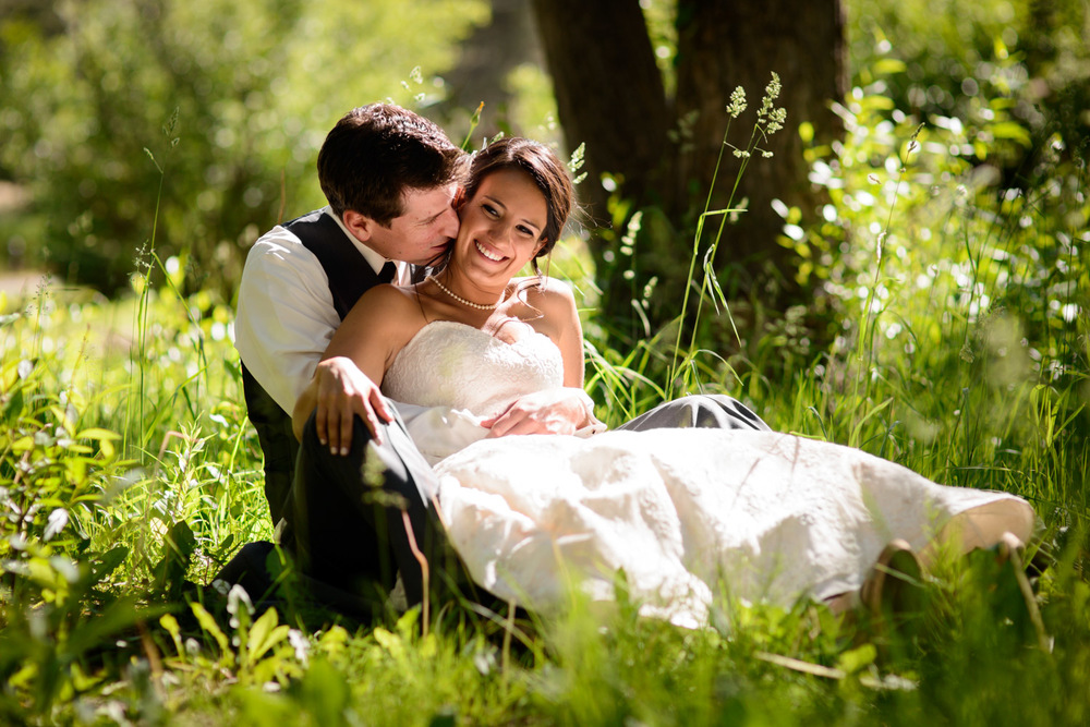sunny bride and groom sit in grass in Estes Park