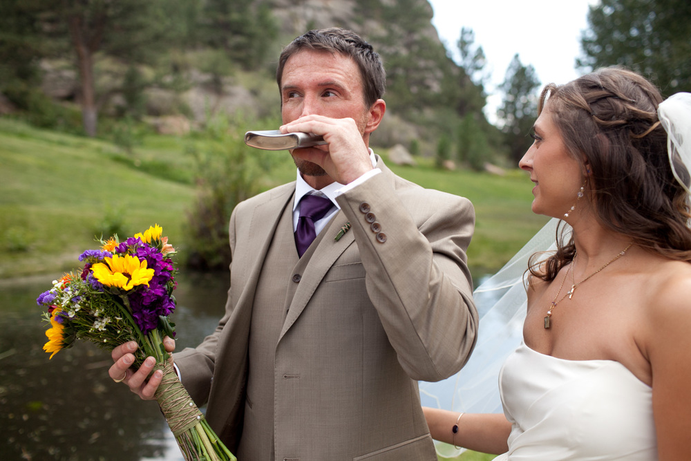 Groom drinks from flask while holding flowers in Estes Park