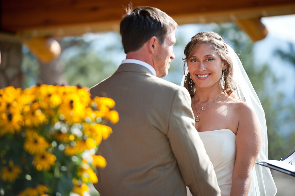 Bride smiles during ceremony with sunflowers