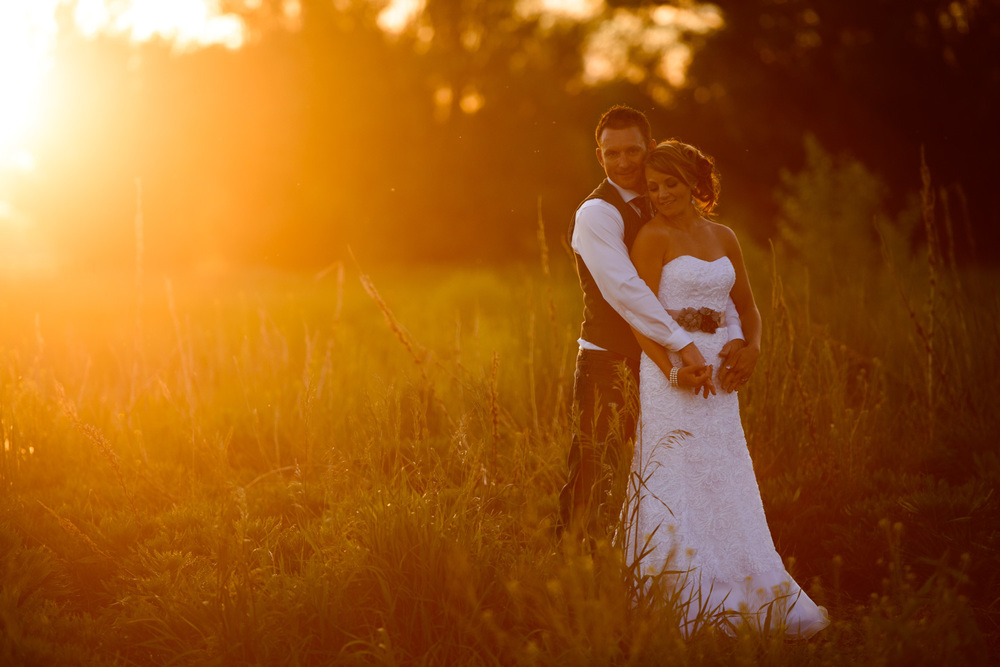 Bride and Groom pose in front of Orange Sunset in Colorado