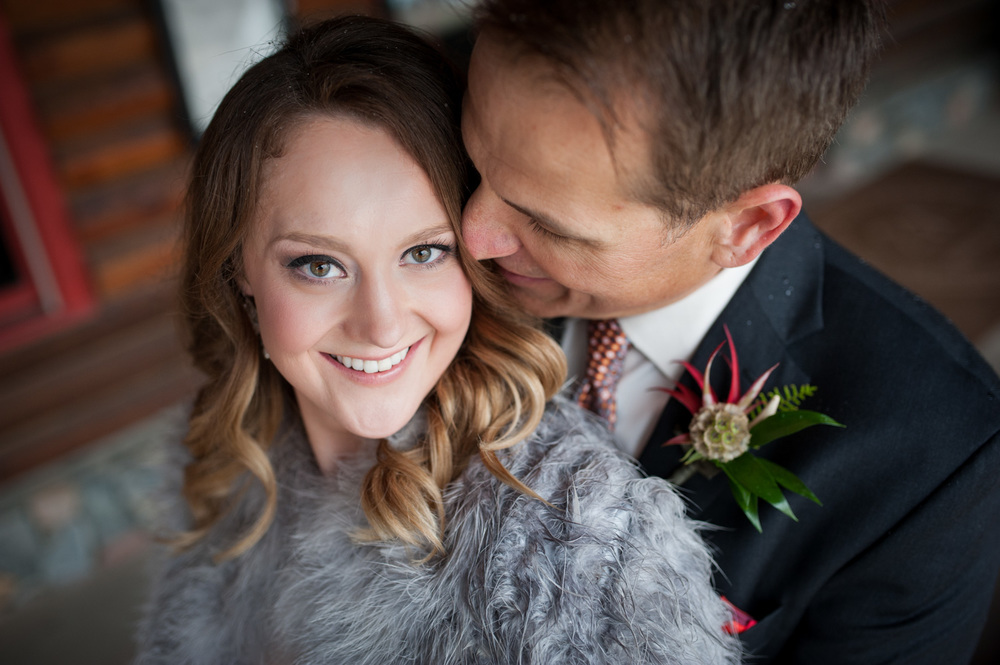 close portrait of groom kissing bride