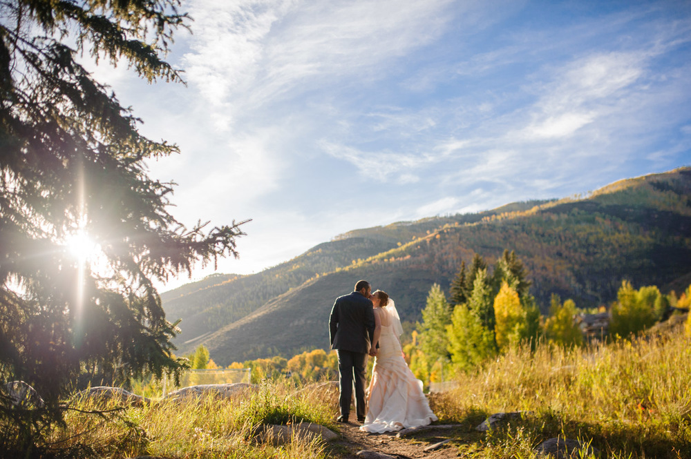 Bride and Groom kiss on mountain trail in Fall