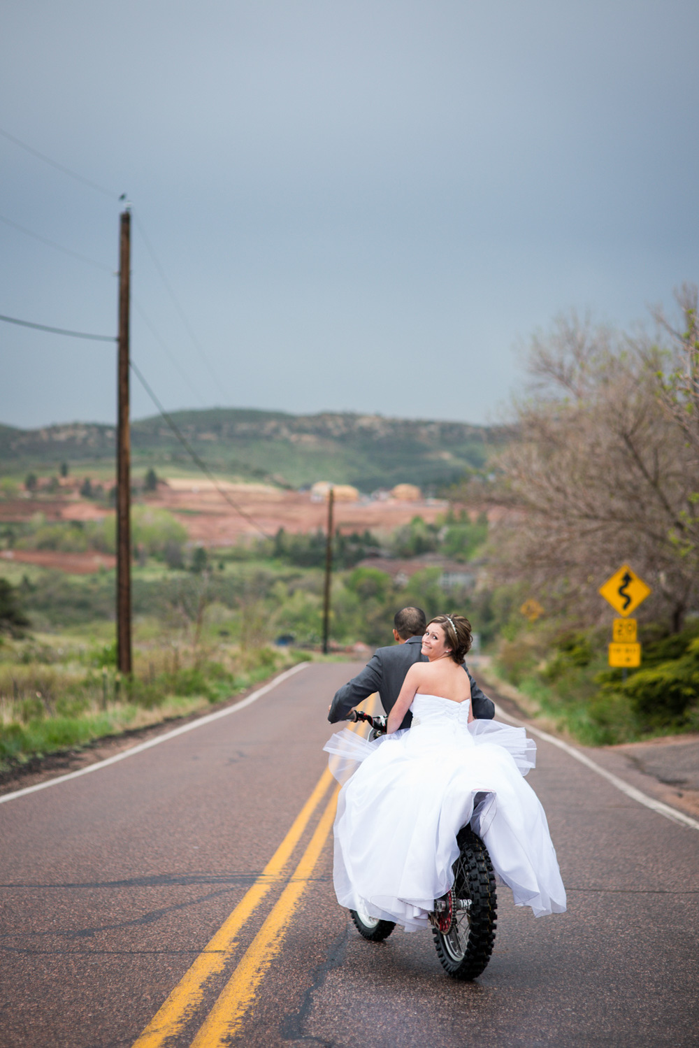Bride and groom ride away on Motorcycle