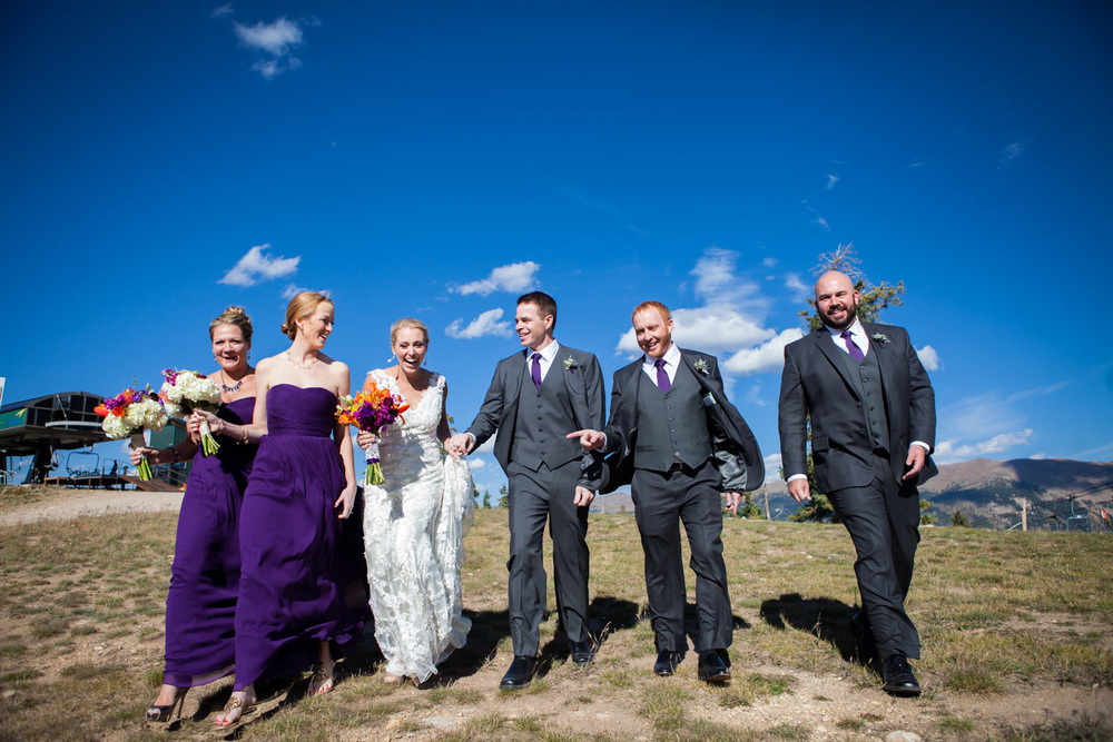 bridal party walking and laughing on Colorado mountain top