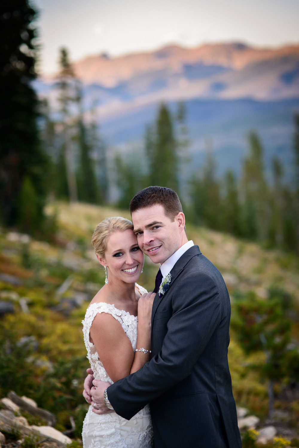 bride and groom pose on Winter Park mountainside