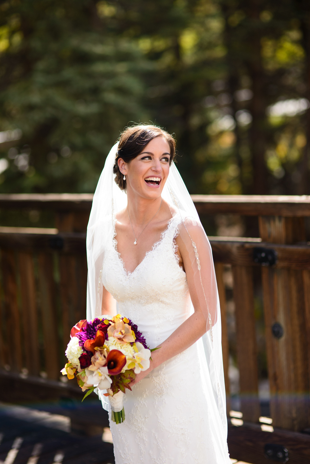 laughing bride on sunny bridge in Vail