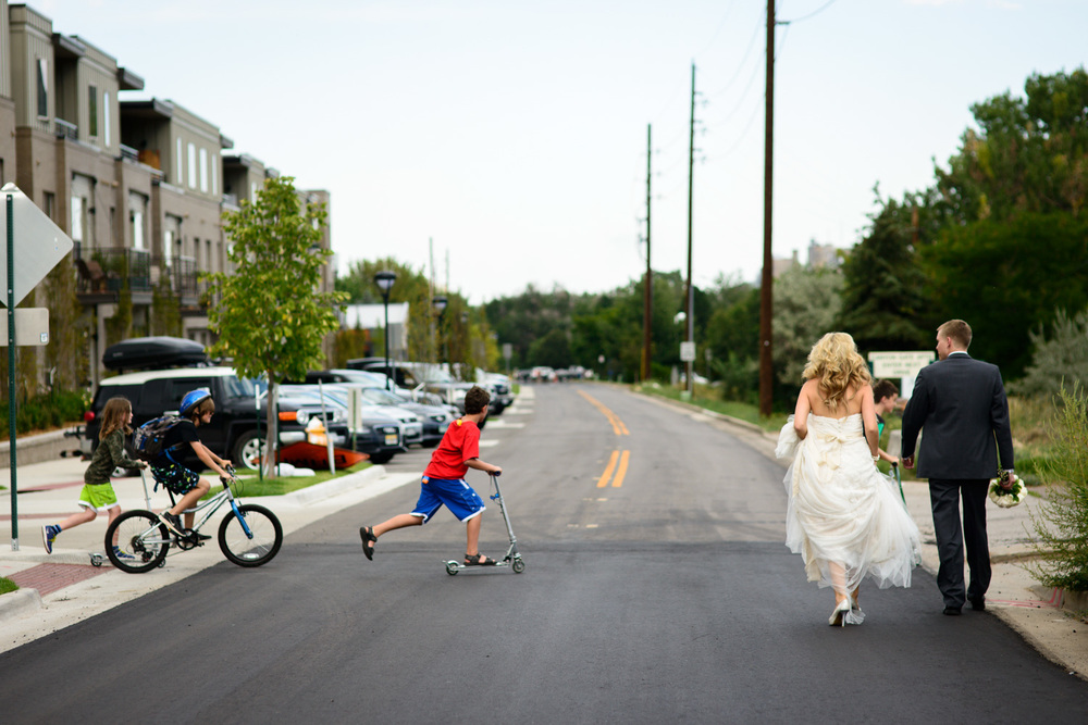kids ride bikes in front of Bride and Groom walking down road