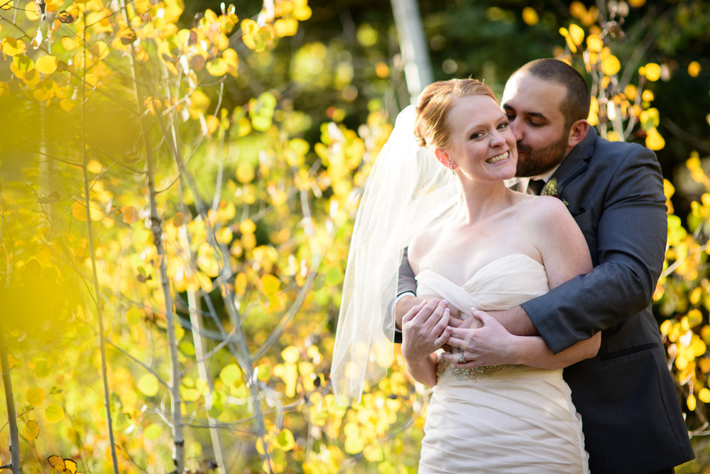 Groom kisses brides cheek in Aspen tree field