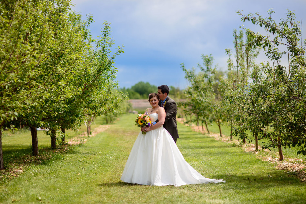 Bride and groom pose between trees at Ya Ya Orchard