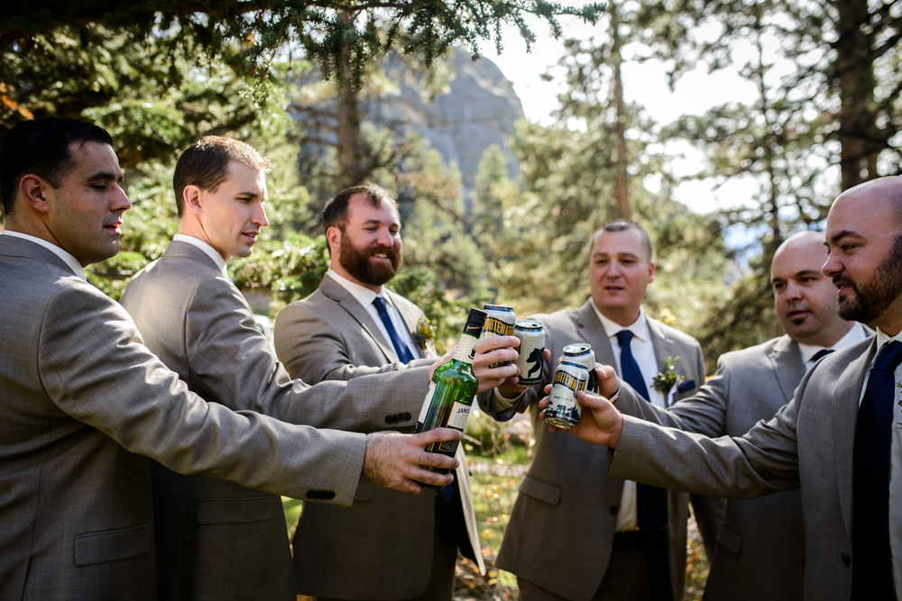 groom cheers beers with groomsmen
