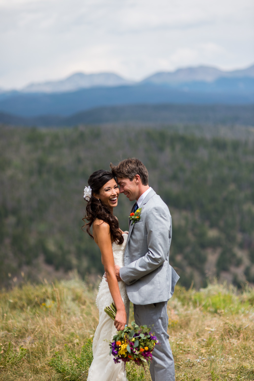 bride laughs with groom on top of mountain near Rocky Mountain National Park
