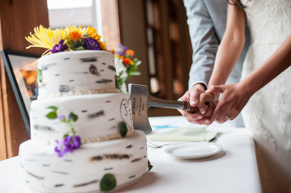 Bride and Groom cut wedding cake with a Hatchet