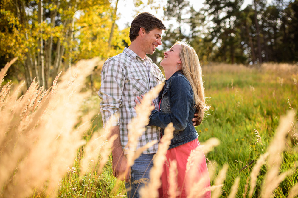 engaged couple look at each other smiling in sunny mountain field