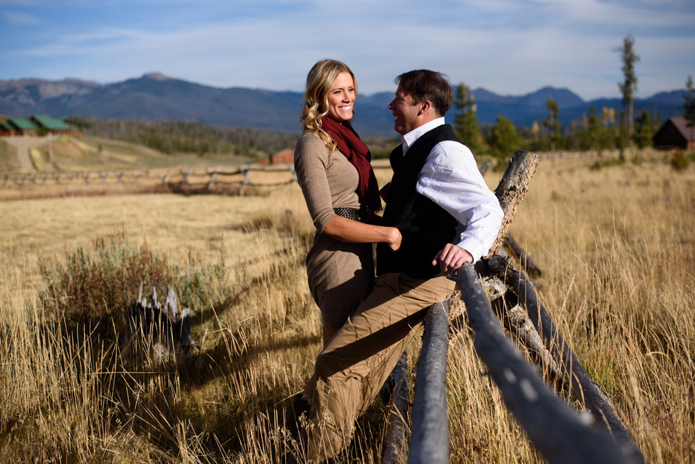 engaged couple lean against wood fence near Granby colorado