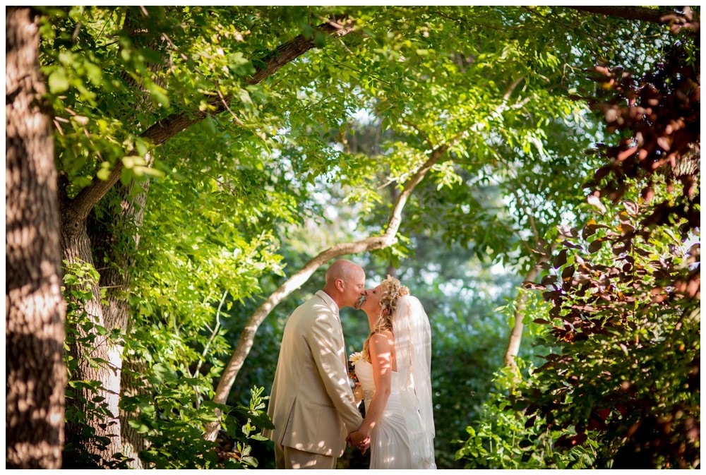 bride and groom kiss under sunny tree tunnel