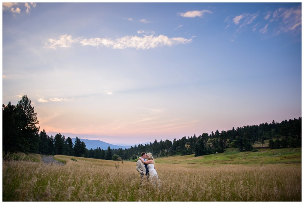 bride and groom in Evergreen meadow at sunset
