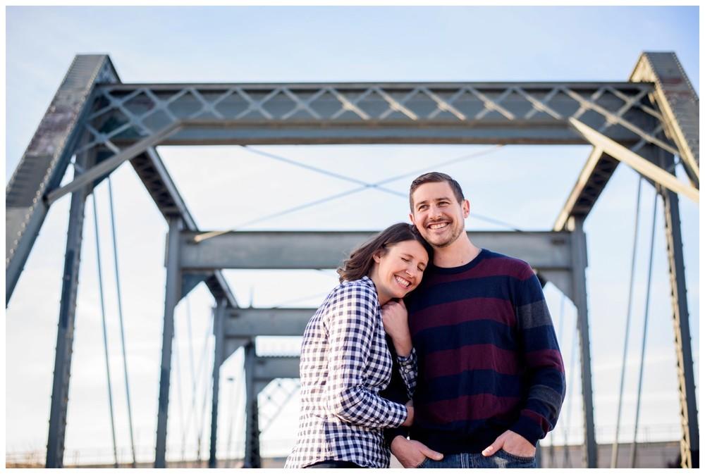 smiling couple hug on downtown Denver Colorado bridge
