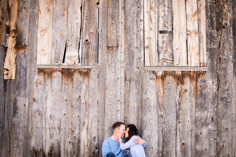 couple kisses on ground in front of old wood barn