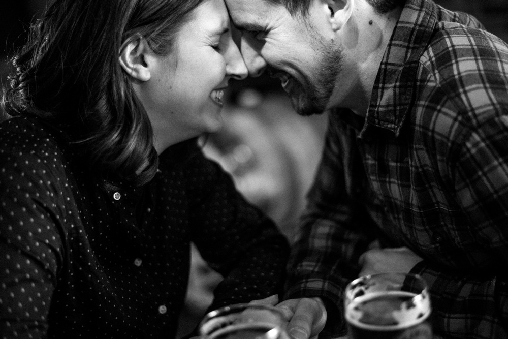 close up black and white photo of laughing couple with beer