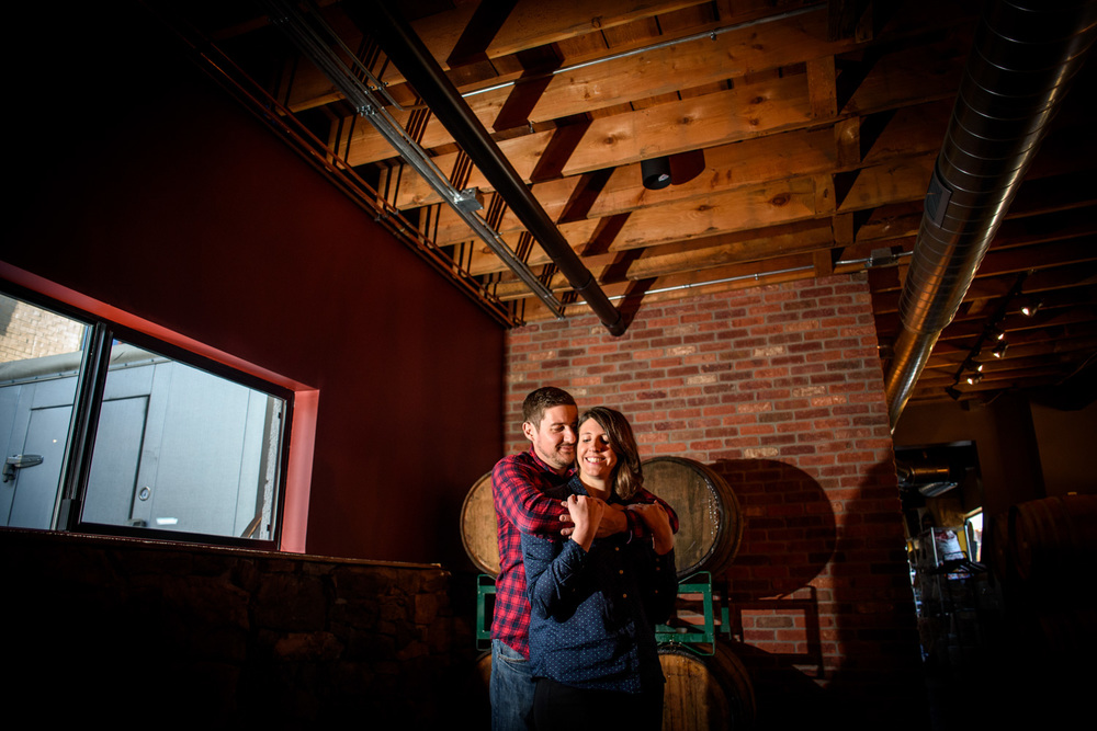 creative photo of engaged couple in Barrel room at Brewery