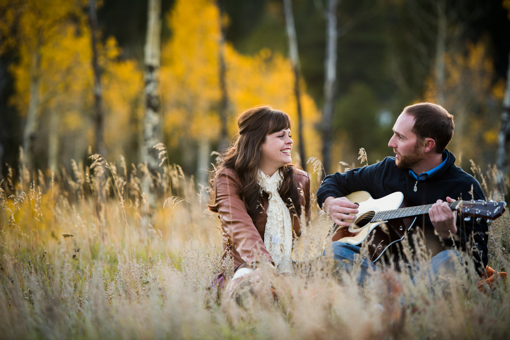 guy plays guitar for fiance in colorado mountain field in Fall