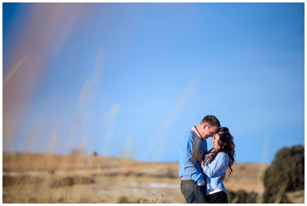 couple put foreheads together in tall grass in Morrison colorado